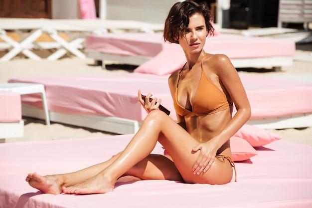 Портрет красивой девушки в бикини, сидящей на пляжной кровати и задумчиво смотрящей в сторону с бутылкой масла для тела в руке. молодая дама в бежевом купальнике загорает, проводя время на пляже