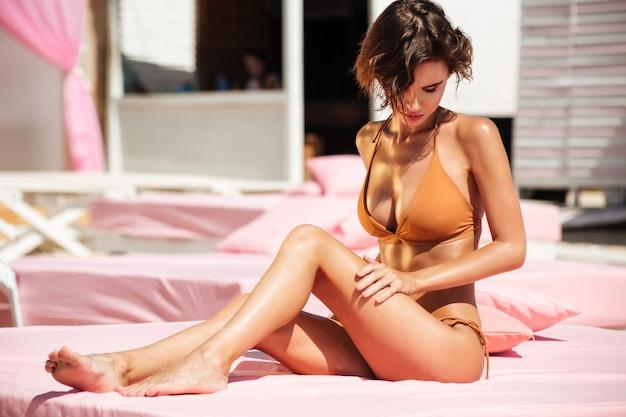 Портрет красивой девушки в бикини, сидящей на пляжной кровати и задумчиво смотрящей в сторону. девушка в бежевом купальнике загорает на пляже. красивая девушка проводит время на пляже