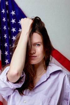미국 국기 벽에 셔츠에 아름 다운 여자의 초상화를 닫습니다