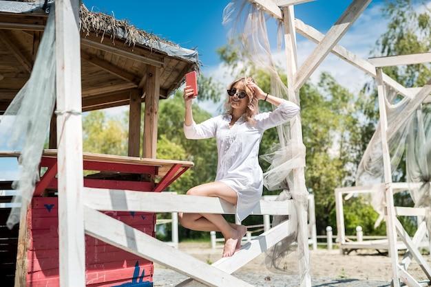 湖の白い木製の望楼で美しい少女の肖像画、自然で楽しんでリラックス