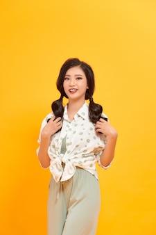 Портрет красивой девушки-модели в повседневной летней одежде без макияжа на желтом фоне