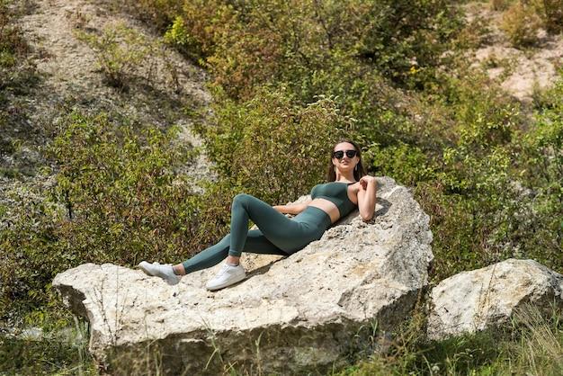 岩、旅行、休日の概念を背景に美しい少女の肖像画