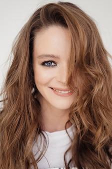 笑顔のフレームで白いストレートルックの美しい少女の肖像画