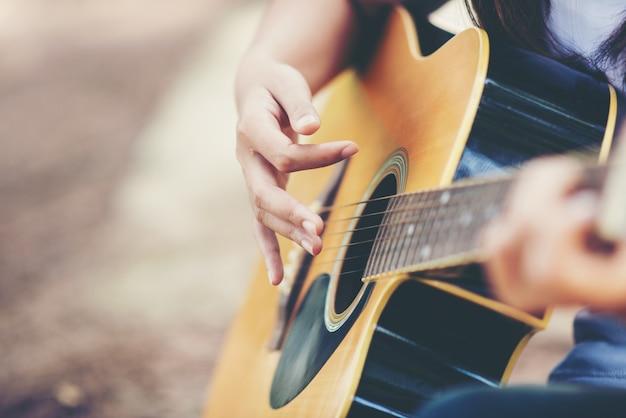 Портрет красивой девушки, играть на гитаре с велосипедом на природе