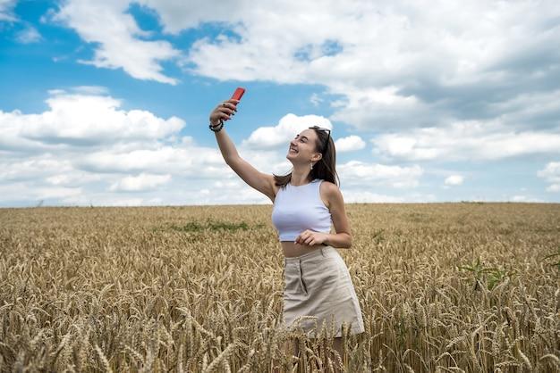 夏の時間を楽しんでいる麦畑でポーズをとって美しい少女の肖像画。自由