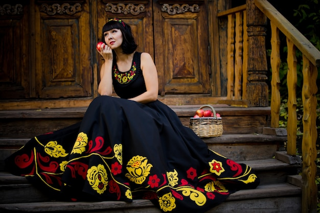 Портрет красивой девушки, сидящей на крыльце старого дома в национальной одежде осенью