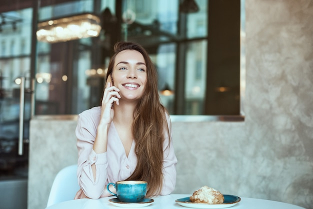 Портрет красивой девушки, используя ее мобильный телефон в кафе.