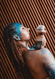 Портрет красивой девушки с синим лицевым боди с блестками. художница рисует на себе боди-арт