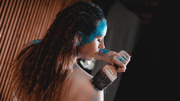 장식 조각과 파란색 얼굴 bodyart와 아름 다운 여자의 초상화. 작가는 자신에게 바디 아트를 그립니다.