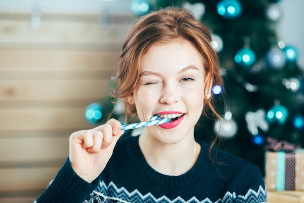 クリスマスツリーの背景に顔の近くにキャンディケインを持つ美しい少女の肖像画