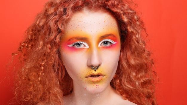Портрет красивой девушки с красочным макияжем и боди-арт