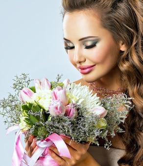 手に花を持つ美しい少女の肖像画。幸せな若い女性は花の花束を保持します
