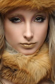 Портрет красивой девушки с золотой макияж в меху