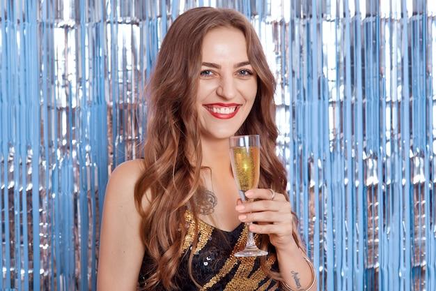 ワインやシャンパンのグラスを持って幸せな魅力的な笑顔、クリスマスと新年の休日のテーマを持つ美しい少女の肖像画 Premium写真