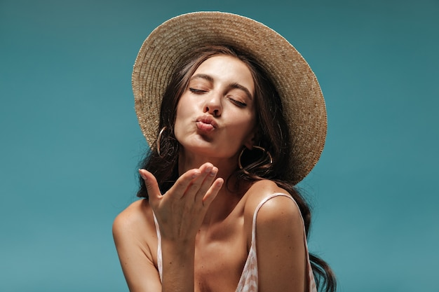 モダンなイヤリングと青い壁に目を閉じてキスを吹くクールなつばの広い帽子の長い髪の美しい少女の肖像画