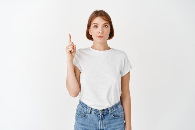 指を上に向けて、自然なメイクで美しい少女の肖像画。白い壁に立って、上に道を示すカジュアルな服を着た若い女性の学生