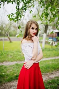 春の花の庭で赤い唇を持つ美しい少女の肖像画は、赤いドレスと白いブラウスを着ます。