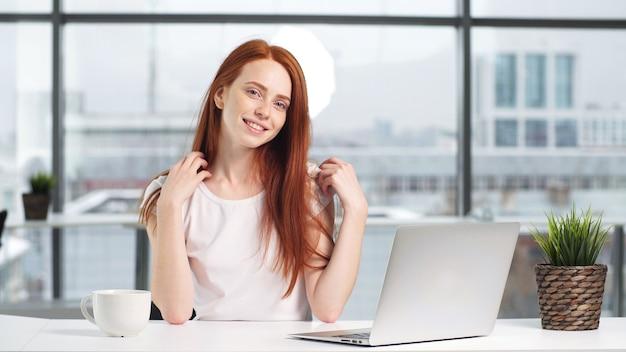 Портрет красивой девушки, работающей на компьютере стол в офисе.