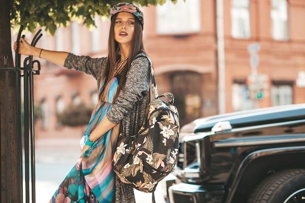 Портрет красивой подростковой модели брюнетки очарования в летней хипстерской одежде и сумке. девушка позирует на улице. женщина в кепке