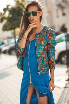 Портрет красивой гламурной современной модели подростка брюнетки в летнем хипстерском синем платье и жакете. девушка позирует на улице. женщина солнечных очков