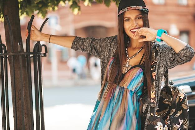 Портрет красивой гламур улыбаясь брюнетка подросток модель в летних битник одежду и сумку. девушка позирует на улице. женщина в кепке