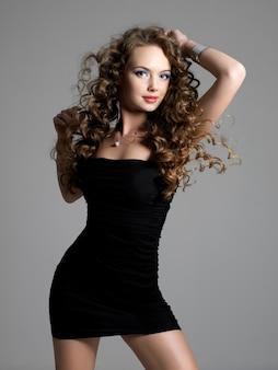 스튜디오에서 포즈를 취하는 긴 곱슬 머리를 가진 아름다운 매력적인 우아함 여자의 초상화