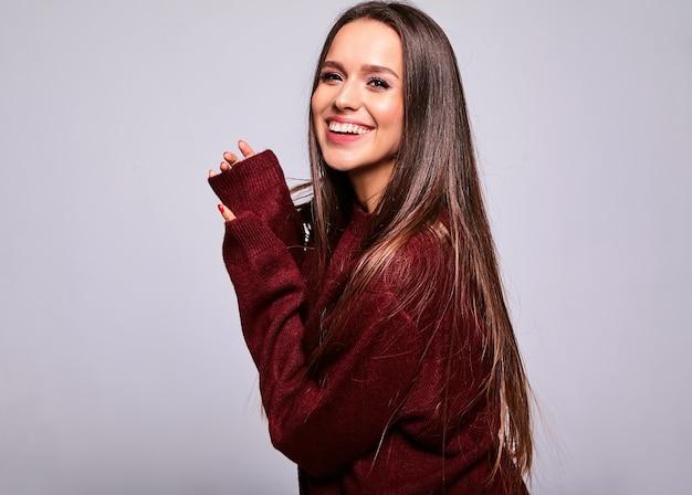 저녁 화장과 화려한 입술 회색에 고립 된 캐주얼 따뜻한 빨간 스웨터 옷에 아름 다운 행복 귀여운 갈색 머리 여자 모델의 초상화
