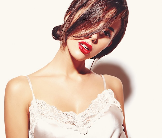 Портрет красивой счастливой милая сексуальная брюнетка женщина с красными губами в пижаме белье на белом фоне