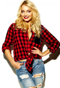 Портрет красивой счастливой милой улыбающейся блондинки плохой девчонкой в красной рубашке битник зимой клетчатой фланелевой рубашке и синих джинсах одежды с красными губами