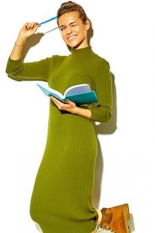 공부하는 동안 생각 다채로운 노트북 파란색 펜을 들고 흰색에 고립 된 캐주얼 녹색 hipster 여름 옷에서 아름 다운 행복 귀여운 웃는 갈색 머리 여자 학생의 초상화