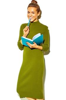 다채로운 노트북과 흰색 물고 파란색 펜에 고립 된 캐주얼 녹색 hipster 여름 옷에서 아름 다운 행복 귀여운 웃는 갈색 머리 여자 여자의 초상화