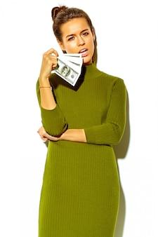 Портрет красивой счастливой милой улыбающейся брюнетки девушки в повседневной зеленой хипстерской летней одежде, изолированной на белом, держащей долларовую банкноту во рту