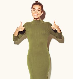 Портрет красивой счастливой милой улыбающейся брюнетки девушки в повседневной зеленой хипстерской летней одежде без макияжа, показывающей большие пальцы вверх знак