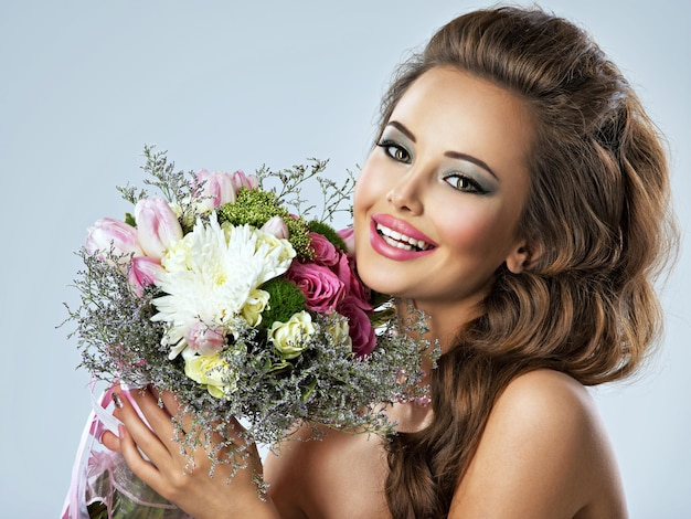 손에 꽃과 함께 아름 다운 행복 한 여자의 초상화. 젊은 매력적인 여자 보유 봄 꽃의 꽃다발