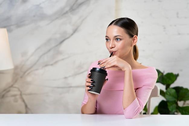 Портрет красивой счастливой девушки, молодой довольно привлекательной женщины, сидящей за столом и наслаждающейся