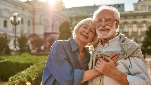 서 있는 동안 서로 결합하고 손을 잡고 있는 아름다운 행복한 노부부의 초상화