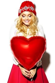 Портрет красивой счастливой сладкой милой улыбающейся блондинки женщины в повседневной хипстерской одежде, в розовой юбке и зимней теплой шапочке с красным сердечным воздушным шаром в руках