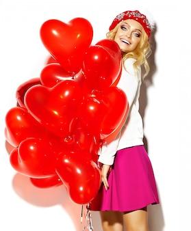 Портрет красивой счастливой сладкой милой улыбающейся блондинки женщины в повседневной хипстерской одежде, в розовой юбке и зимней теплой шапочке с красными сердечными воздушными шариками в руках