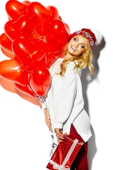 Портрет красивой счастливой сладкой улыбающейся блондинки, держащей в руках большую рождественскую подарочную коробку и сердечные воздушные шарики в повседневной красной хипстерской зимней одежде, в белом теплом свитере