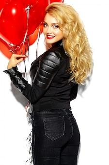 Портрет красивой счастливой сладкой улыбающейся блондинки девушка держит в руках красные сердечные воздушные шары в повседневной черной хипстерской одежде