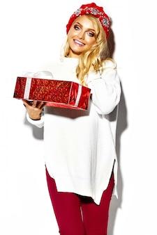 Портрет красивой счастливой сладкой улыбающейся блондинки женщина держит в руках большую рождественскую подарочную коробку в повседневной красной хипстерской зимней одежде, в белом теплом свитере