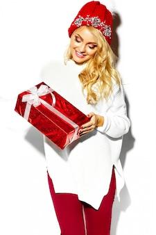 白い暖かいセーターで、カジュアルな赤いヒップスター冬服で大きなクリスマスギフトボックスを彼女の手で保持している美しい幸せな甘い笑顔金髪女性女性の肖像画