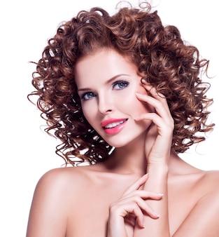 Портрет красивой счастливой женщины с представлять вьющиеся волосы брюнет - изолированный на белизне.