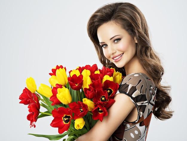 손에 꽃과 함께 아름 다운 행복 한 여자의 초상화. 젊은 매력적인 젊은 여자 보유 빨간색과 노란색 튤립 꽃다발