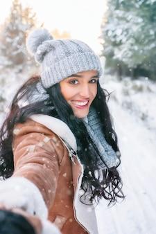 冬、ライフスタイル、冬、クリスマスまたは新年のテーマの森の美しい幸せな若い女性の肖像画