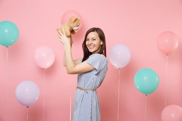 Портрет красивой счастливой молодой женщины, носящей голубое платье, держащей плюшевую игрушку плюшевого мишку на пастельно-розовом фоне с красочными воздушными шарами. праздник дня рождения, концепция искренних эмоций людей.