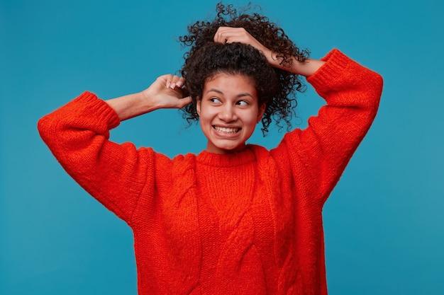 ポニテールで長く暗い巻き毛のウェーブのかかった髪の手で集まる美しいヒスパニック系ラテン系女性の肖像画