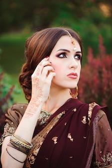 아름다운 인도 여자의 초상화입니다. 문신 멘디와 쿤단 보석 젊은 힌두교 여자 모델. 인도 전통 의상 사리.