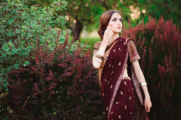 Портрет красивой индийской девушки. модель молодой индуистской женщины с татуировкой менди и украшениями кундан. традиционный индийский костюм сари.