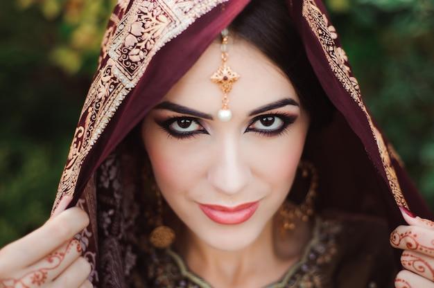 아름다운 인도 여자의 초상화입니다. 문신 멘디와 쿤단 보석 젊은 힌두교 여자 모델